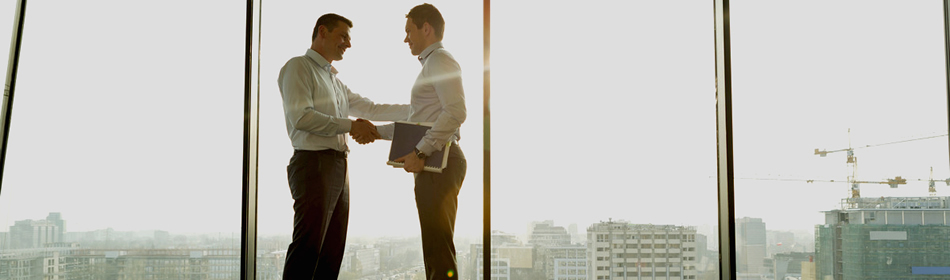 Two men shaking hands in front of skyscraper window